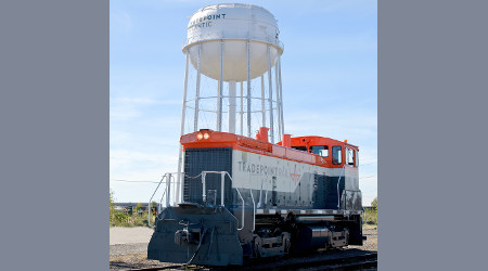 Tradepoint locomotive rests near a water tower